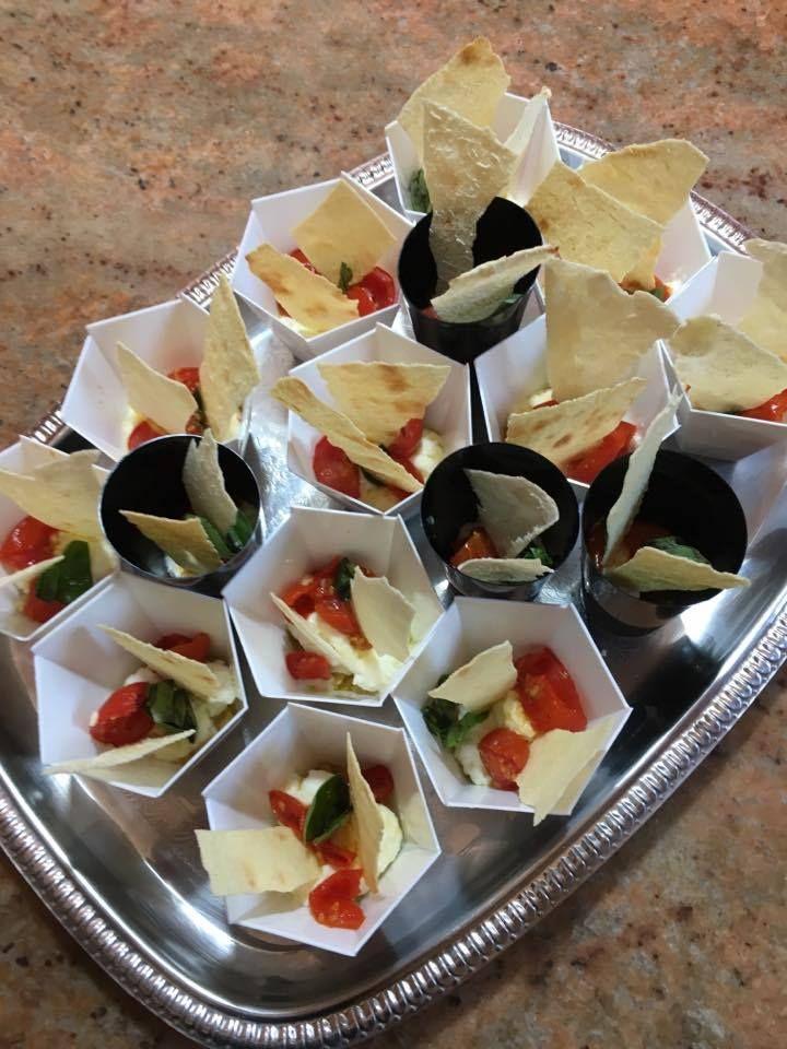 Buffet rustico per festa in giardino: bicchierini di burrata, pomodorini gratinati e pane carasau
