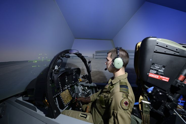The Royal Canadian Air Force (RCAF) is exploiting advances in modeling and simulation (M&S) technology to improve its training and readiness as well as increase its operational output. Captain Sébastien Tremblay Verreault, a CF-18 fighter pilot during a session on a CF-18 simulator that is located at 3 Wing Bagotville, Quebec. The simulator is operated by L3 MAS (Military Aviation Systems) and is used by Canadian fighter pilots for their training and qualifications.