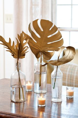 Spray paint large leaves with gold paint for glam centerpieces. Check and check.