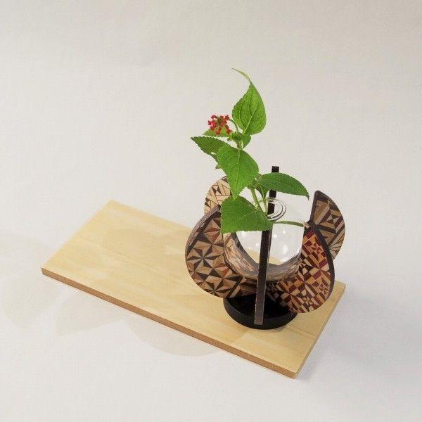 日本の伝統工芸品 箱根寄木細工の「フラワーベース」です。サイズ:D92mm×W92mm×H82mm日本製(有限会社 木路)木製/ガラスフラワーベース、花瓶・一輪挿しとしてお使いになれます。野の花や愛らしい木の芽をほんの少しいただいて、玄関やリビングの片隅に花を添えるのはいかがでしょうか?フラワーベースの形も、花開いたような素敵な形。見る角度によって異なる景色を楽しむのも良いですね。また、フラワーベースをアロマディフューザーとしてお使いいただくのも新しい使い方。お好きな香りをガラスに入れて、お部屋のかくれた主役になりますよ。専用箱入りですので、新築・引っ越し・独立のプレゼントにもお勧めです。■掲載写真はイメージです。本商品は天然木を使用し手作りで生産されております。そのため一つ一つ寄木の色合いや柄の出方が異なります。ご了承のうえお求めいただきますようお願い申し上げます。