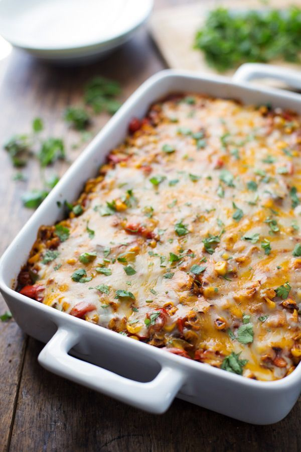 mexican casserole with bell peppers, corn, refried beans, corn tortillas, enchilada sauce, and cheese