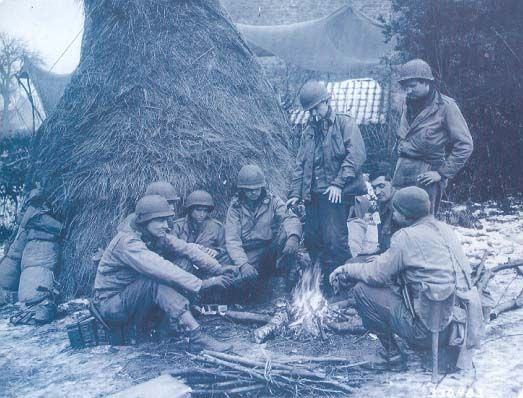 Infantrymen of the 83rd Infantry Division warm themselves around a fire near Fays, Belgium, on January 3, 1945. Fays was finally secured, along with Ferme de Menil, on January 15.