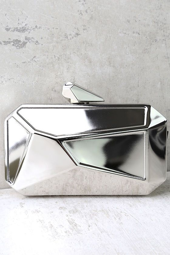 """Get noticed with the What a Rock Silver Clutch! Shiny silvermetal shapes this faceted box clutch with a matching clasp closure. Interior (with accordion sides) has just the right amount of room for all your essentials! Carry as a clutch or attach the 46"""" long silver chain strap."""