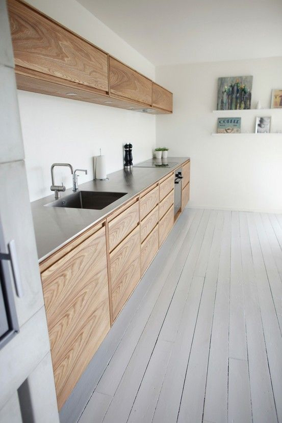 Une cuisine en longueur, où le seul luxe est le placage bois des portes.