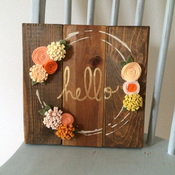 Hello Wooden Sign  Stained wooden sign. Painted wreath with felt flowers frame the gold Hello word! Great to hang on a wall or stand on a