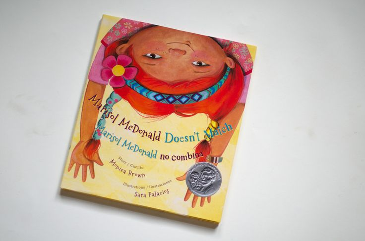 "Marisol McDonald Doesn't Match/Marisol McDonald no Combina by Monica Brown, illustrated by Sara Palacios.  ""One of our favorite characters of all time, Marisol McDonald, struggles with her identity (and what other people say about her) as a soccer-loving, paint-slinging, bilingual, biracial (Scottish-Peruvian-American) girl. She wrestles through with class and spunk, and is loveable, inspiring, and endearing."" One of the very best bilingual children's books out there."