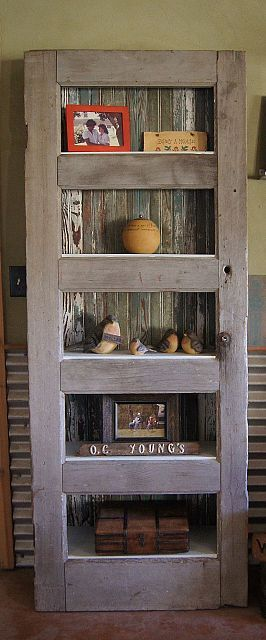 Old weathered door and floor boards used to create a leaning shelf.
