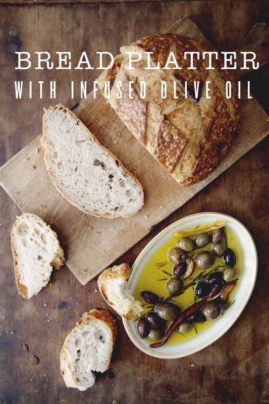 Bread Platter with Infused Olive Oil   1 cup olive oil 2 garlic cloves 1 sprig rosemary 1 dried chili 1 lemon peel 1 cup mixed olives 1 loaf of bread, sliced