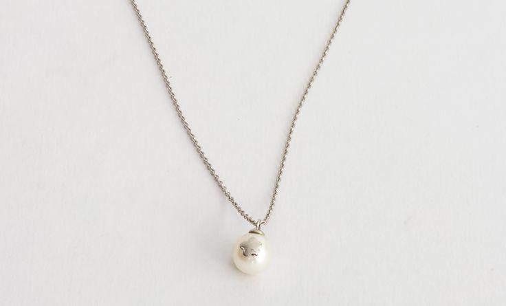 Cadena de plata con incrustación en plata con forma de flor sobre perla blanca.