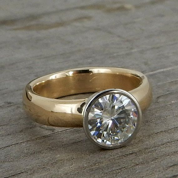This gorgeous sparkler features a huge and fiery Forever Brilliant™ moissanite (7mm; equivalent to a 1.25 carat diamond) set in a 950 palladium bezel on a 4mm x 2mm comfort-fit 14k yellow band with a polished finish. All of the metal used in the construction of this ring is from recycled sources. As you can see in the fourth photo, the bezel I use for this design combines the best aspects of a full bezel setting (a clean, seamless, modern look that protects the stone and wont scratch your…