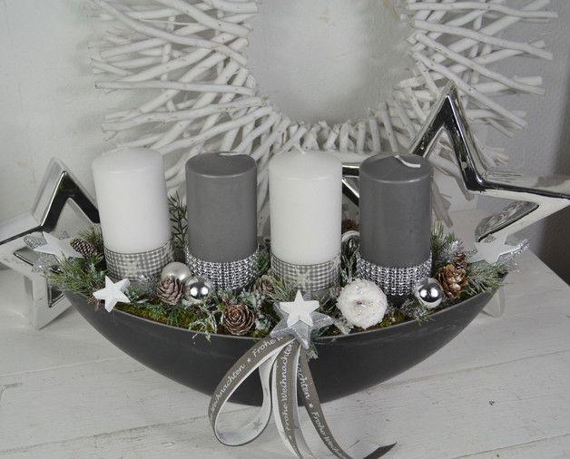 Hallo zusammen! Wir bieten Euch hier einen schönes Adventsgesteck in einer Schale an. Eine Schale Schieferoptik (Schiffchen, oval) mit 4 Kerzen (Kerzenbrennschutz) wurden mit Strass- und…