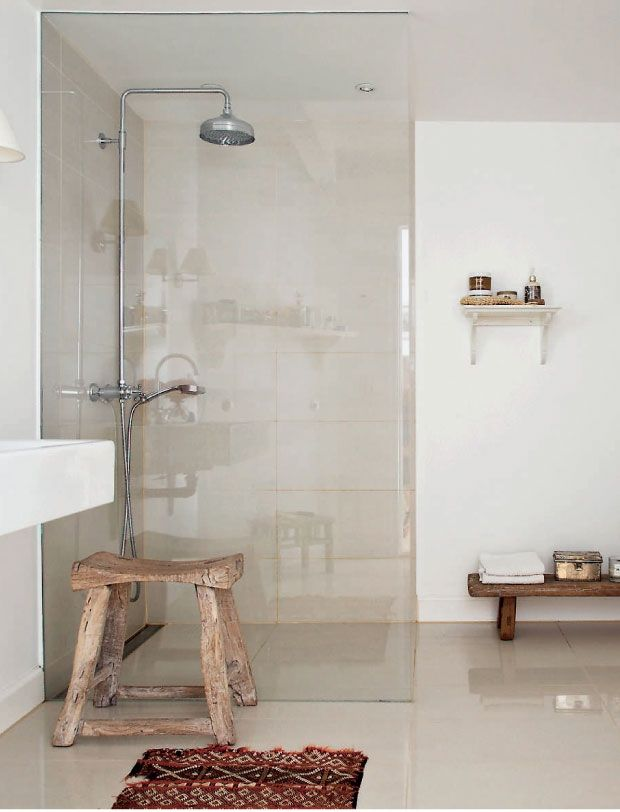 Beige shiny bathroom with walk-in shower and rustic wood benches