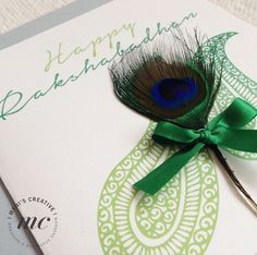 Handmade Rakhi Card Fusing a modern pattern with a traditional peacock feather, hand finished with a ribbon. A New Rakshabadhan Card collection.