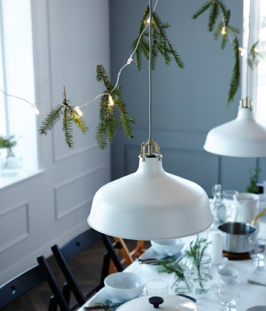 Want to win a few wows with your table setting? Decorating above the table helps make a super cozy and intimate celebration. We've used hanging lights and pine branches.