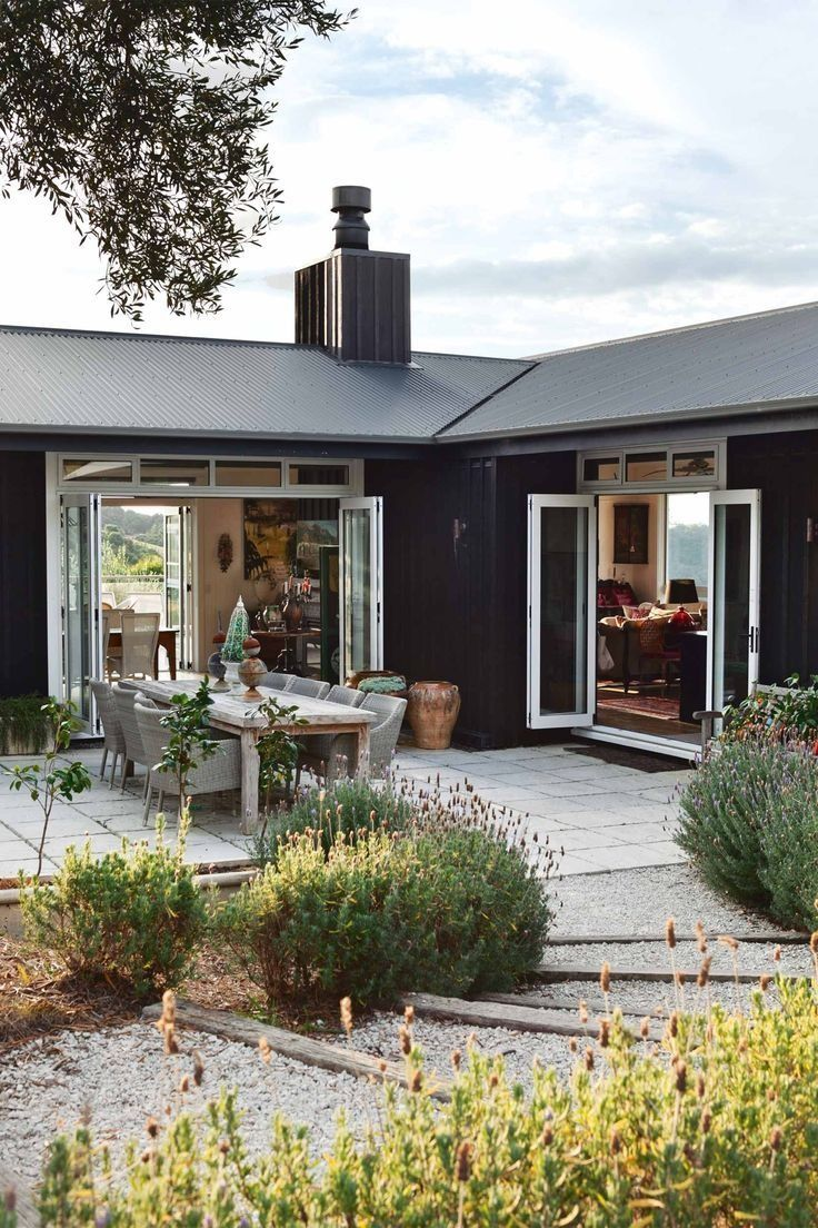 Love the contrast between the matte black exterior and bright white window trim of this modern farmhouse home.