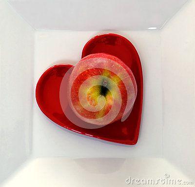 A single apple on a heart shaped plate on a white plate