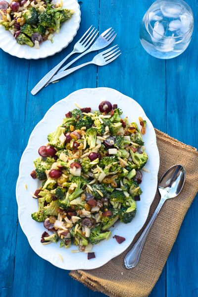 This crunchy broccoli salad recipe is packed with crunchy bits of bacon, grapes, almonds and raisins. We lightened it up by swapping half the mayonnaise with greek yogurt and swapping the white sugar for honey. It also holds well for days making it the perfect make ahead side dish!