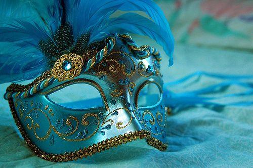 Blauw masker et gouden details en blauwe veren