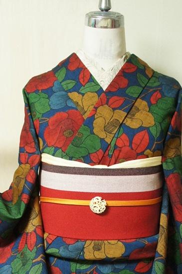 スモークがかったネイビーにディープブルーの地に、芥子色やこっくり緑、落ち着いた朱赤で染め出された、愛らしい椿のモチーフが染め出されたウールの単着物です。