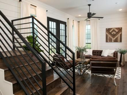 This informal den, adjacent to the main dining room on the main floor, blends modern styled chairs and sofa with traditional elements like classic styled ceiling fans and dark hardwoods.