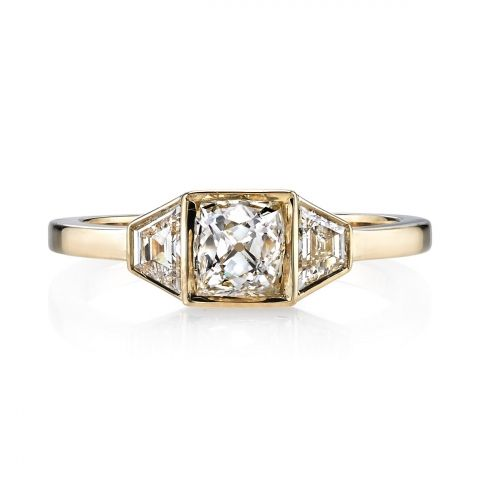 0.76ct I/VS vintage Cushion cut diamond set in a handcrafted 18K yellow gold mounting. A clean and classic design featuring trapezoid accent diamonds.