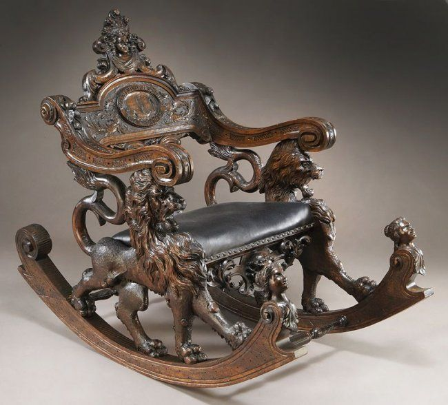 "Columbian Exposition carved walnut Fantasy rocker the back having a crest with carved face and feather headdress over a horizontal splat with carved griffins centering a carved oval plaque of a sailing ship and reading, ""World's Columbian Exhibition 1492. Chicago. 1892."