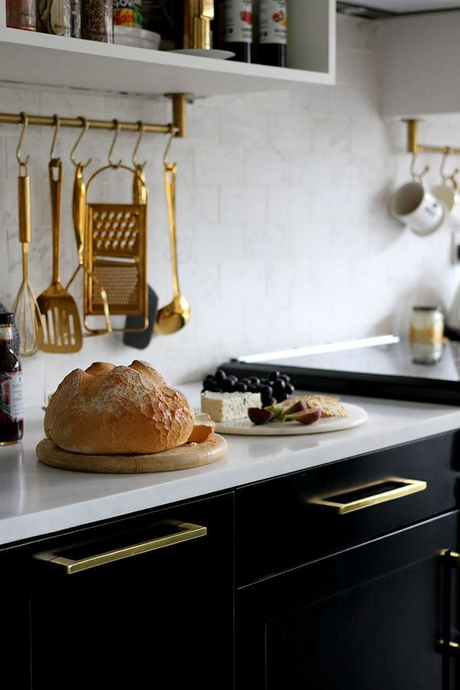 marble effect tiles and countertop with black kitchen cabinets and gold cabinet handles and gold hanging utensils
