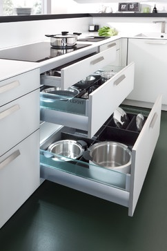 Side panel, bar top and niche shelves are made from a continuous black worktop. The floor units with matt white glass fronts are encased within. Narrow contrast: the Corian worktop only 13 mm thick.
