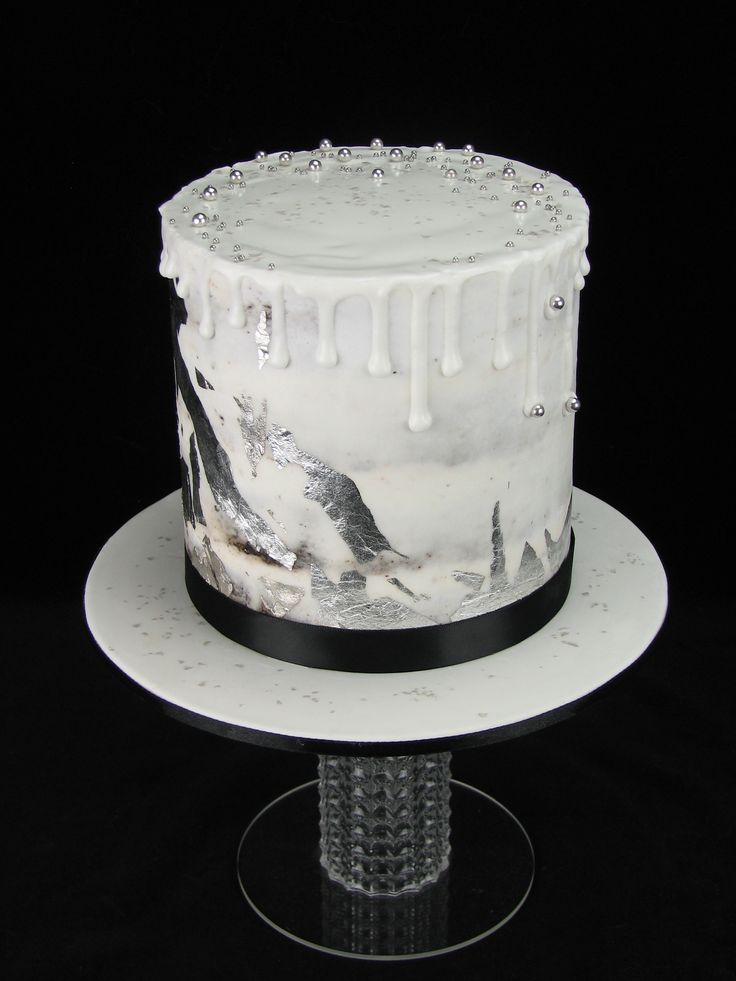 Black and white and silver theme for a baby shower.  This is a semi naked chocolate mud cake with white buttercream and royal icing drip. Edible silver leaf and cachous added for sophistication. www.facebook.com/cakesbyleannerhodes