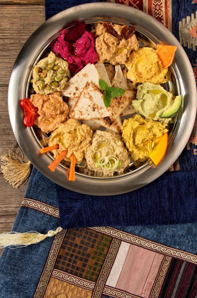 Tra le specialità mediorientali, per l'Hummus abbiamo un debole particolare. Soprattutto se può essere servito in 8 modi diversi! La base è sempre la stessa: salsa #tahini, #ceci, succo di #limone, #yogurt bianco, olio d'oliva, sale e aglio.  Fatte 8 porzioni separate aggiungendo in ognuna l'ingrediente speciale: #barbabietole, #peperone, #porro, #carote, #patata dolce, #pomodori secchi, #avocado, #pistacchi. E il #Rainbow #Hummus è pronto!