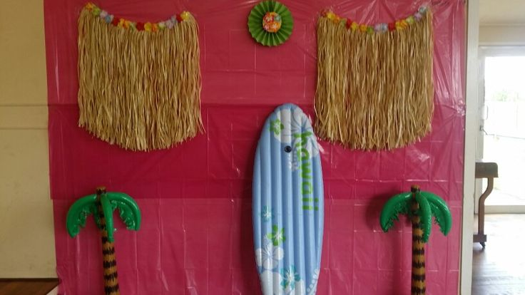 The results of the Hawaiian Luau Baby Shower I planned: Backdrop for photos - inflatable surfboard and palm trees from the discount store, grass skirts and pink plastic table cloths from KMart
