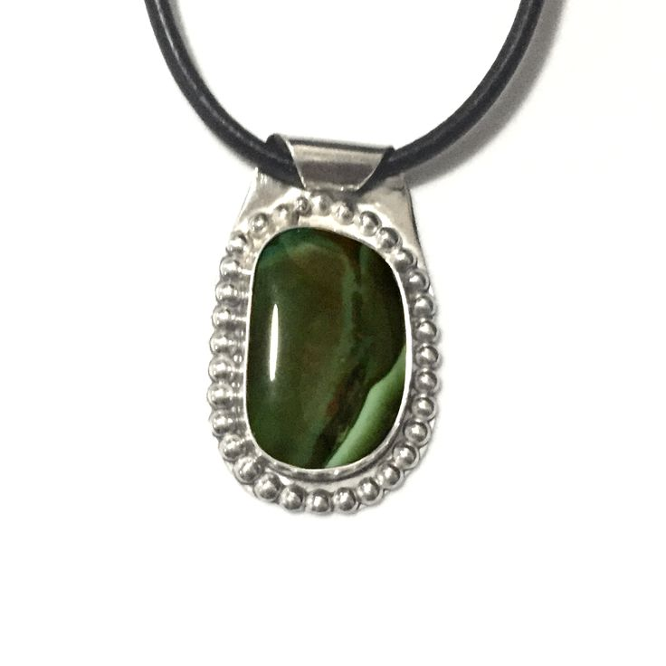 Sterling Silver and Authentic Natural Green Turquoise Pendant on Leather Necklace This pendant features a beautiful, natural, Paradise Nevada, turquoise cabochon gemstone set in sterling silver. The turquoise is beautiful dark green with a little light blue banding and a soft wave of burnt umber running down the center of the stone. It will make…