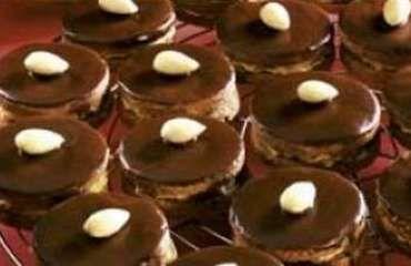 Ischelské dortíky 21 dkg hladké mouky 2 dkg kakaa 7 dkg mletého cukru 1špetka vanilkového cukru (tak na špičku nože) 4 dkg mletých ořechů 14 dkg másla špetka mleté skořice (nemusí být) mandle na ozdobení čokoládová poleva