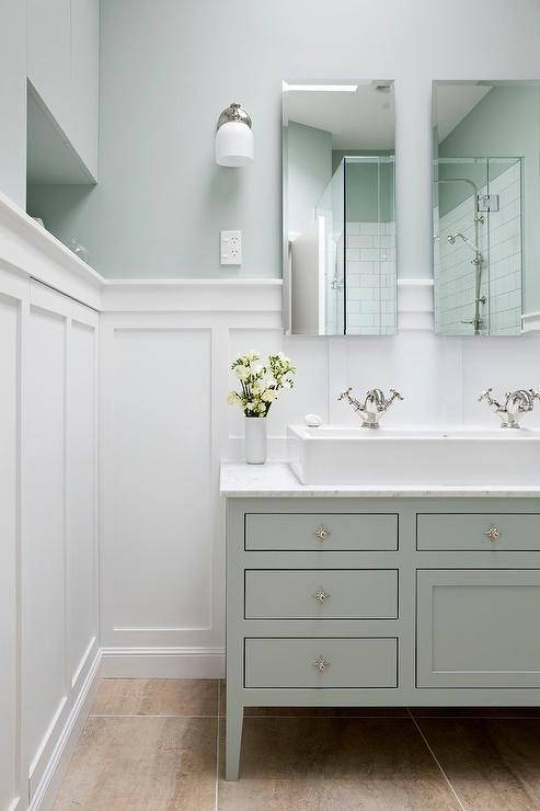 Soothing bathroom features top half of walls painted green and lower half of walls clad in board ...