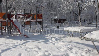 Children's playground in the park covered by snow.