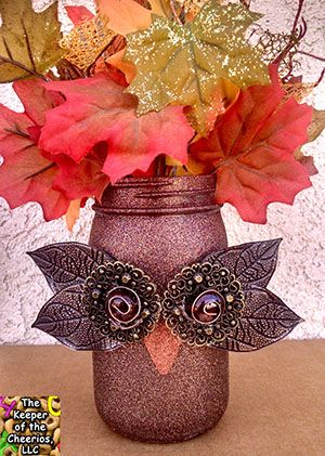 FALL OWL MASON JAR Materials: Mason Jars, glitter blast spray paint , metal leaves (found on ebay), glass marbles or gems, wire, metal sheet for beak, metal findings and dollar store flowers. (looking for the glitter spray CLICK HERE for where I purchase mine) Make sure your jars are clean then simply spray them with the glitter spray and let dry for 24 hours. Once dry you can embellish them any way you want. All Items where glued on with hot glue or glass glue. -For the owl eyes I layered…