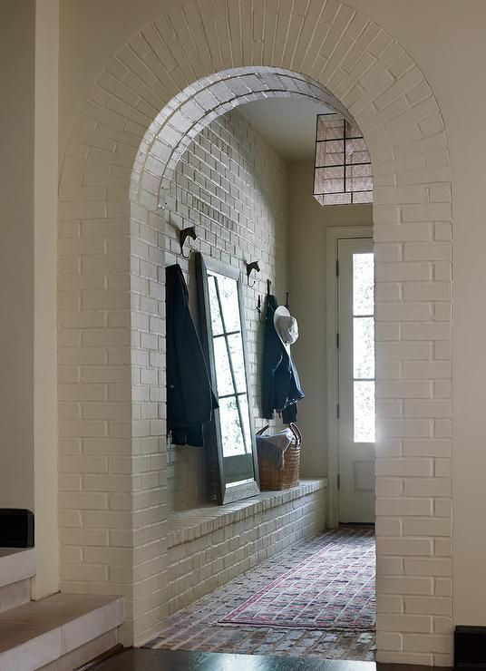 A white brick arched mudroom door way opens to red brick floor tiles covered in a red rug placed in front of a built-in white brick bench topped with a full length mirror leaning against a white brick wall between two iron horse coat hooks.