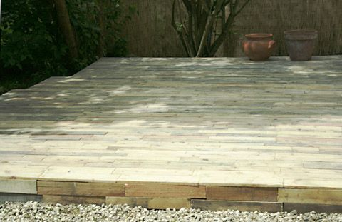 a very rustic wooden ground level deck made from wood pallets, great for garden patio's large or small, install a deck with extremely low cost as wood pallets are free for the taking