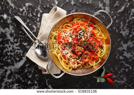 tasty Pasta Spaghetti with Meatballs and tomato sauce and Parmesan cheese on a dark background in a small iron skillet