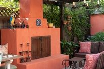 southwest style interior design - I love this outdoor space with the clay fireplace and accents. The fireplace tools are wrought iron. This is a great example of Southwestern interior design.
