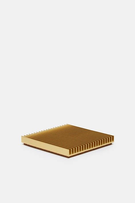Designer Shaun Kasperbauer, co-founder of Brooklyn-based Souda, refines traditional tabletop accessories to their architectural essence. This ribbed square of chromate-conversion-coated aluminum is produced through a unique partnership with a manufacturer of industrial heat sinks. Each cork-backed trivet is the result of a common yet complex manufacturing technique reimagined so as to combine the industrial and the domestic.