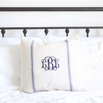 "Add some modern farmhouse charm to your home with this lovely pillow cover. Pictured is a 18"" by 18"" pillow cover over a 20"" IKEA pillow insert. Please specify your monogram at the checkout. Personalization For Couple: Husband's initial, Last name initial, Wife's initial For Individual: First name initial, Last name initial, Middle name initial Product Description Blue: a beige pillow cover with two vertical navy stripes and a monogram in the center of the two stripes. Lette..."