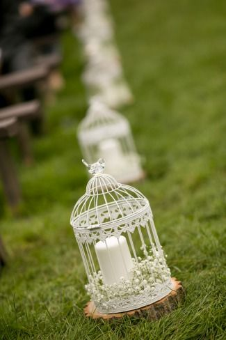 Striking aisle decor: white birdcages with candle and baby's breath on wood round