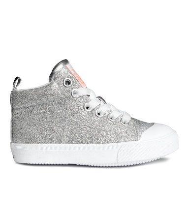 Silver. Ett par ankelhöga sneakers. De har vadderad kant och hälla bak. Resårsnörning fram. Foder och innersula i textil. Yttersula i gummi.