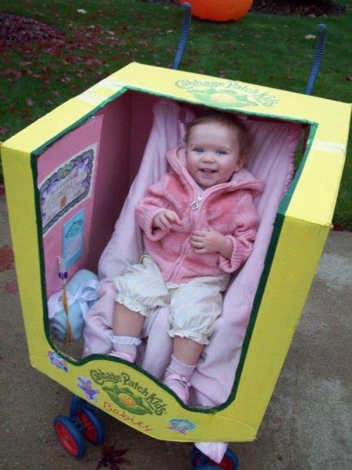 Disfraz de bebé. Muñeca y su caja en el carrito de bebé