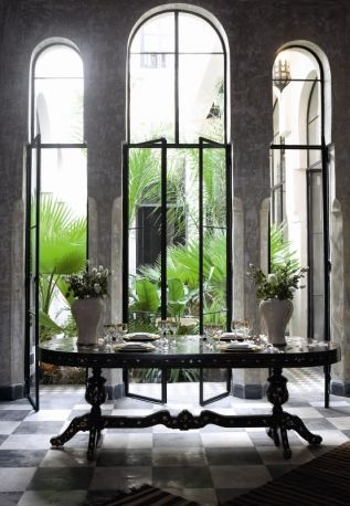 A riad in Marrakech. Lounge room overlooking the wooden table inlaid in ivory and mother-of-Pearl, three arched doors open onto the courtyard garden.