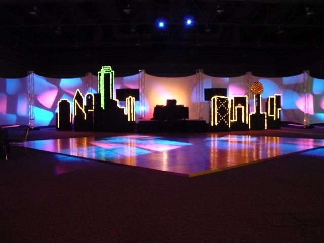 An illuminated city backdrop can add local feel to the stage and showcase the destination.