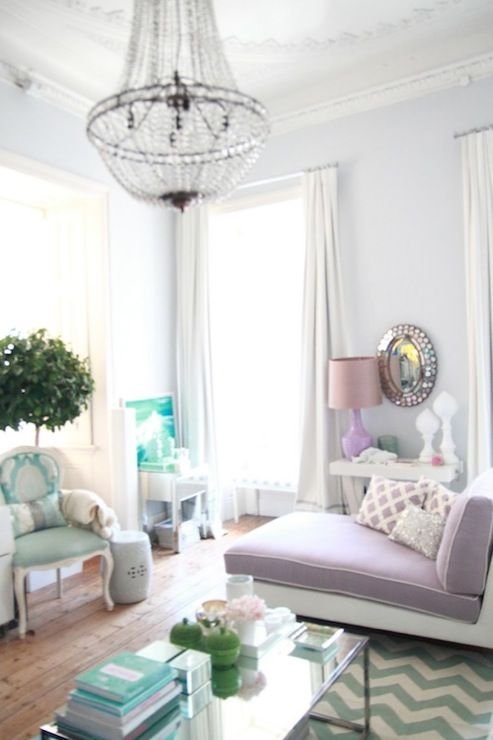 living rooms - glossy white lacquer console table purple lamp oval mirror gray walls lilac purple chaise lounge white piping ivory teal blue zigzag chevron rug turquoise blue Louis chair white garden stool crystal chandelier