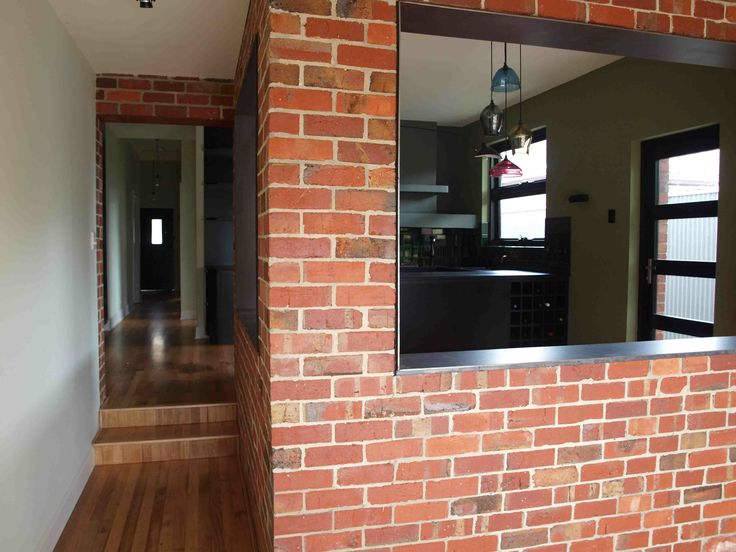 View from rear of house to front door, exposed brick with steel inserts framing dinning area.