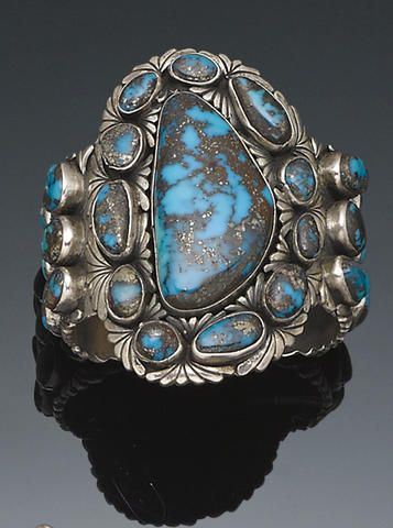A Navajo bracelet by Alice Platero : the thick cuff with a profusion of turquoise nuggets set amongst silver overlay leaf forms and stamped drop accents.